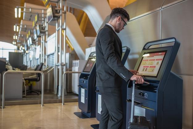 Jeune Homme D'affaires Faisant L'auto-vérification Dans Une Machine à L'aéroport Photo Premium