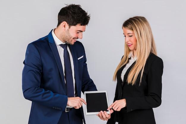 Jeune homme d'affaires et femme d'affaires, pointant son doigt sur une tablette numérique sur fond gris Photo gratuit