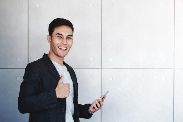 Jeune homme d'affaires heureux souriant et montrer les pouces en utilisant un smartphone Photo Premium