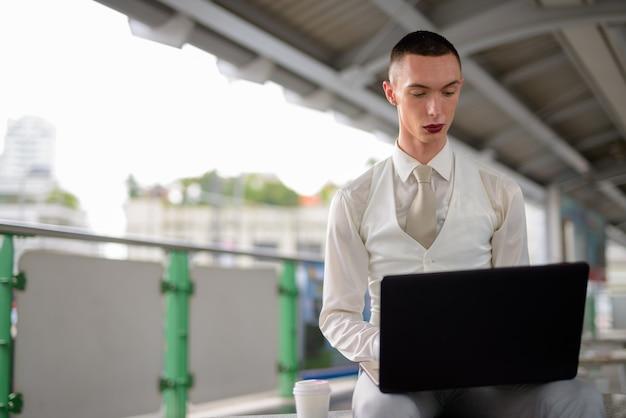 Jeune Homme D'affaires Homosexuel Androgyne Lgtb à L'aide D'un Ordinateur Portable Photo Premium