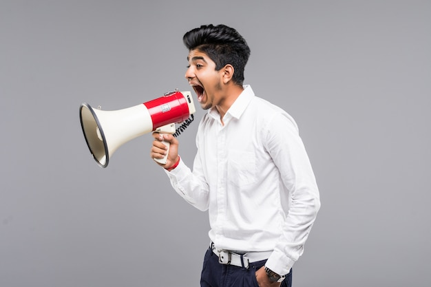Jeune Homme D'affaires Indien Annonçant Dans Un Mégaphone Sur Mur Gris Photo gratuit