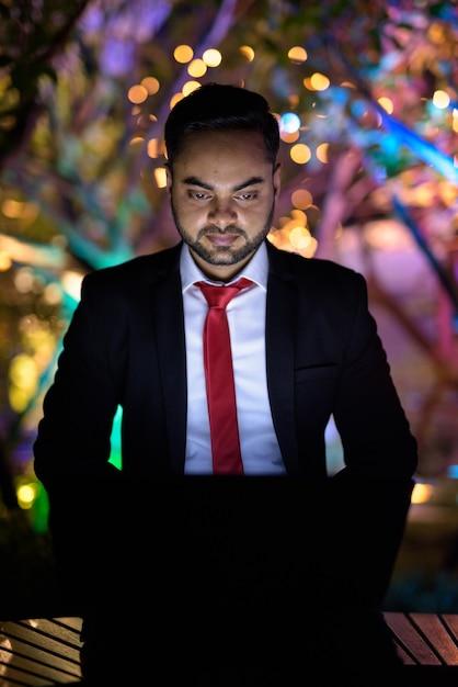 Jeune Homme D'affaires Indien Barbu Contre Vue Sur La Ville Pendant La Nuit Photo Premium