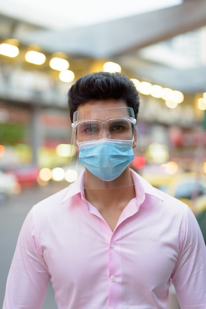 Jeune Homme D'affaires Indien Portant Un Masque Et Un écran Facial Dans Les Rues De La Ville à L'extérieur Photo Premium