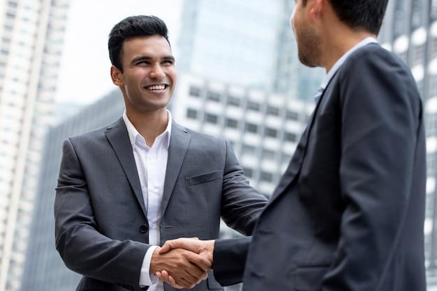 Jeune homme d'affaires indien souriant, faisant la poignée de main avec partenaire Photo Premium