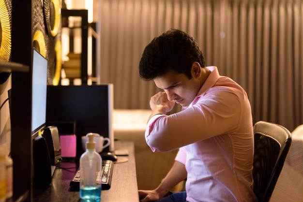 Jeune Homme D'affaires Indien Tousse Sur Sa Manche Tout En Faisant Des Heures Supplémentaires à La Maison Pendant La Quarantaine Photo Premium