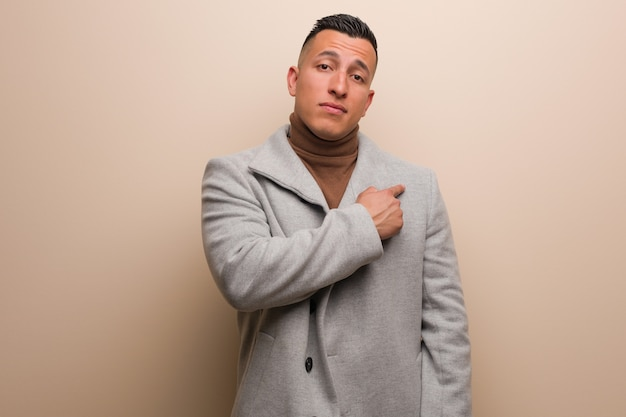 Jeune homme d'affaires latin souriant et pointant sur le côté Photo Premium