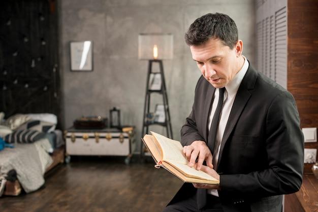 Jeune homme d'affaires avec livre de détente à la maison Photo gratuit