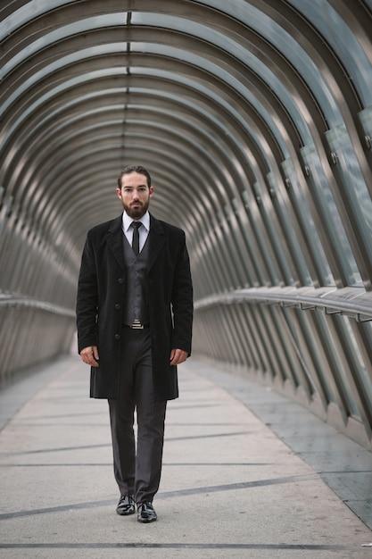 Jeune homme d'affaires marchant sur un pont piétonnier futuriste dans le quartier de la défense. paris, france. Photo Premium