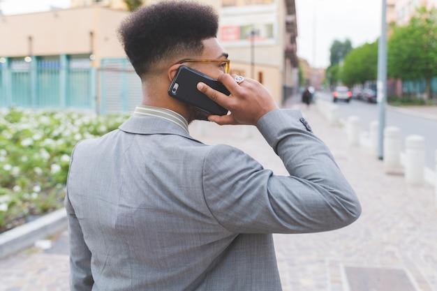 Jeune homme d'affaires noir en plein air parlant de téléphone intelligent Photo Premium