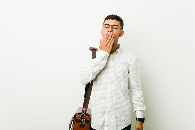 Jeune homme d'affaires occasionnel hispanique bâillement montrant un geste fatigué couvrant la bouche avec la main. Photo Premium