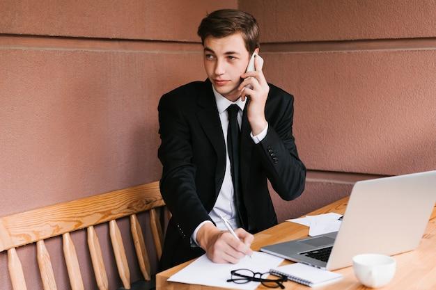 Jeune homme d'affaires parlant au téléphone au bureau Photo gratuit