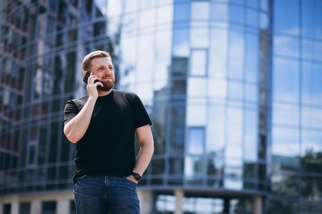 Jeune homme d'affaires parlant au téléphone près du gratte-ciel Photo gratuit