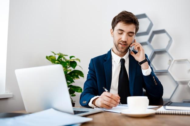 Jeune Homme D'affaires Prospère, Parlant Au Téléphone, Fond De Bureau. Photo gratuit