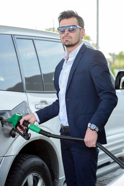 Jeune homme d'affaires, ravitaillement en carburant à la station d'essence. Photo Premium
