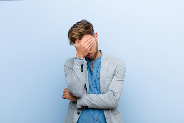 Jeune homme d'affaires à la recherche de stressé, honteux ou contrarié, avec un mal de tête, couvrant le visage avec la main contre le bleu Photo Premium