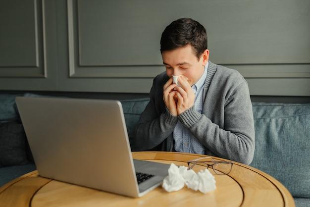 Jeune homme d'affaires se mouche le nez en travaillant sur son ordinateur portable au travail. Photo gratuit
