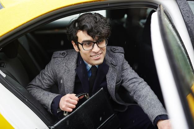 Jeune homme d'affaires souriant, laissant le taxi sous la pluie Photo gratuit