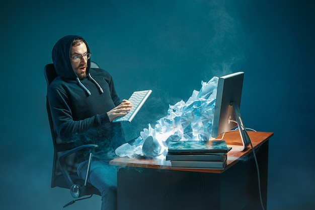 Jeune Homme D'affaires Stressé Beau Travaillant Au Bureau Dans Un Bureau Moderne Criant à L'écran D'ordinateur Portable Et En Colère Contre Le Spam Photo gratuit