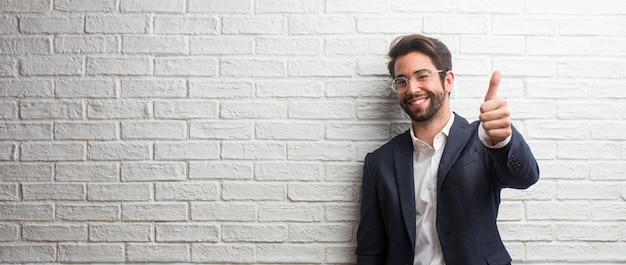 Jeune homme d'affaires sympathique gai et excité, souriant et levant le pouce vers le haut, concept de réussite et d'approbation, geste ok Photo Premium