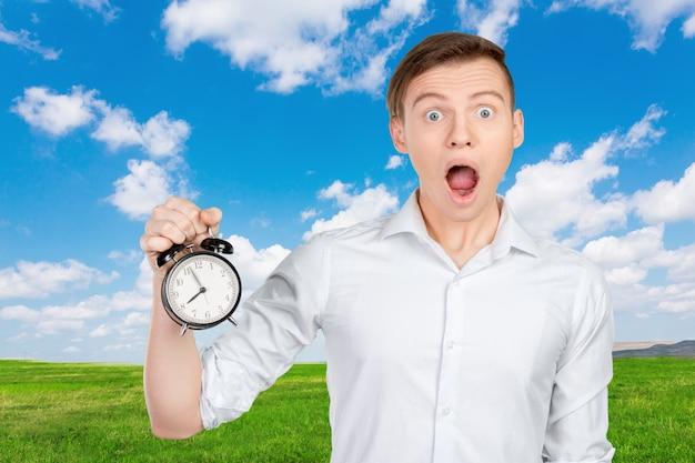 Jeune homme d'affaires tenant une horloge Photo Premium