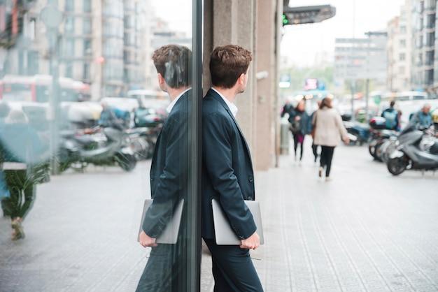 Jeune homme d'affaires tenant une tablette numérique à la main se penchant sur le verre Photo gratuit