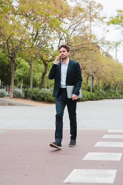 Jeune, homme affaires, tenue, ordinateur portable dans main, parler, sur, téléphone portable, marcher, route Photo gratuit