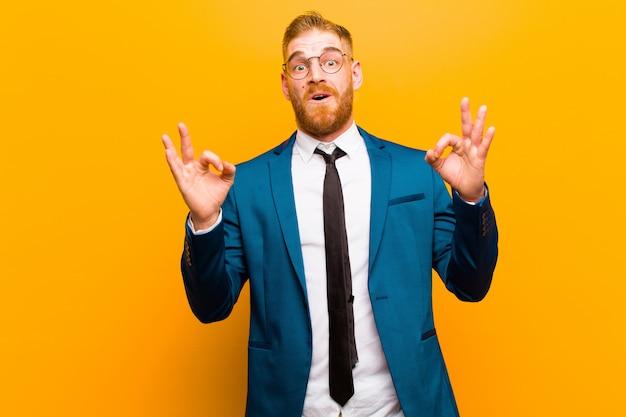 Jeune Homme D'affaires à La Tête Rouge Se Sentant Choqué, Surpris Et Surpris, Montrant Son Approbation, Faisant Signe D'accord Avec Les Deux Mains Contre Orange Photo Premium