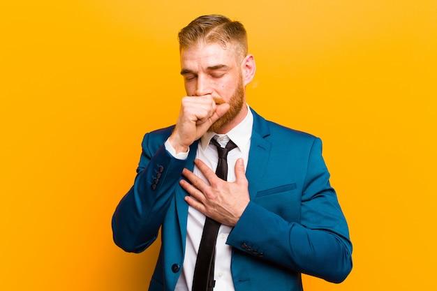 Jeune homme d'affaires à la tête rouge se sentir malade avec mal à la gorge et la grippe, tousser avec la bouche couverte Photo Premium
