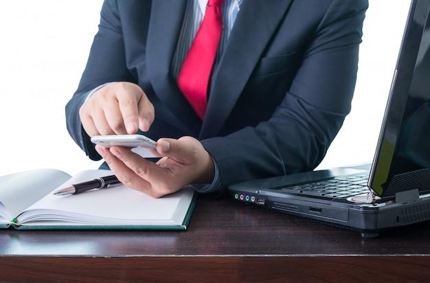 Jeune homme d'affaires travaillant avec des appareils modernes, smartphone et ordinateur portable Photo Premium