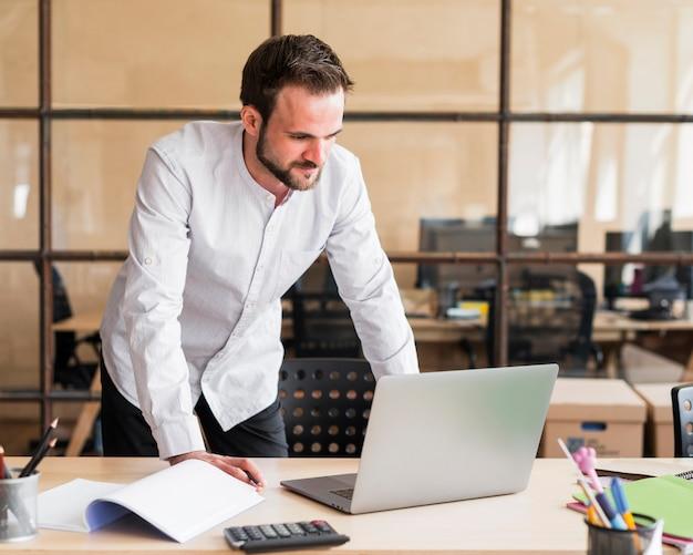 Jeune homme d'affaires travaillant avec un ordinateur portable au bureau Photo gratuit