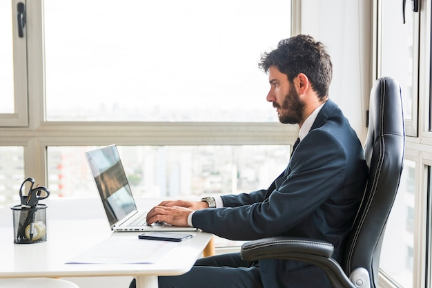 Jeune homme d'affaires travaillant sur un ordinateur portable sur le lieu de travail Photo gratuit