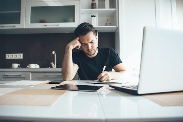 Jeune Homme D'affaires Travaille à Distance De La Maison Dans La Cuisine à L'aide D'un Ordinateur Portable Tout En écrivant Quelque Chose Photo Premium