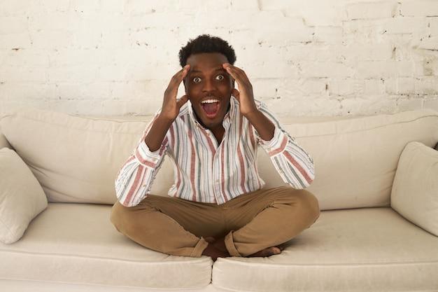 Jeune Homme Africain Excité Extatique Assis Dans Le Salon Se Tenant La Main Sur Sa Tête, S'exclamant Wow, Omg, étant Impressionné Photo gratuit