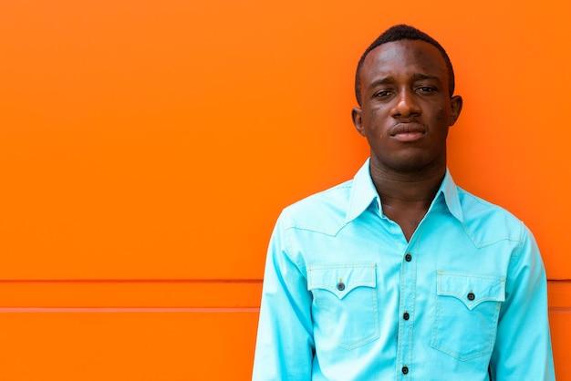 Jeune Homme Africain Noir Appuyé Contre Un Mur Peint En Orange Photo Premium
