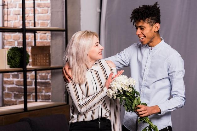 Un jeune homme africain propose sa petite amie en donnant un bouquet de fleurs blanches Photo gratuit