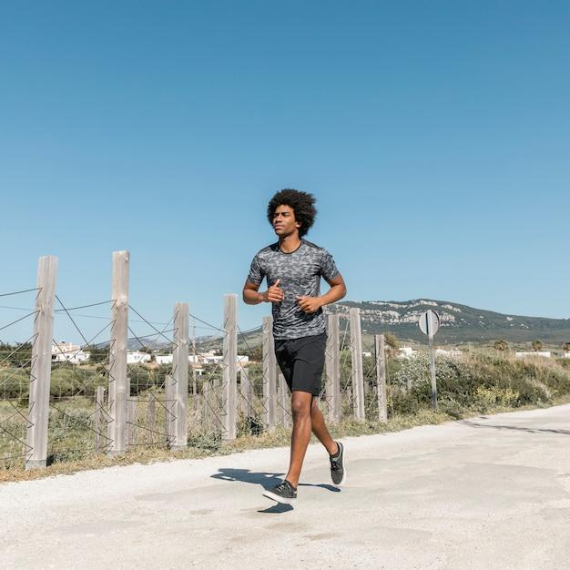 Jeune homme africain qui court le long de la route Photo gratuit