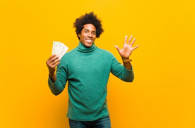 Jeune homme afro-américain avec billets d'un dollar contre dos orange Photo Premium