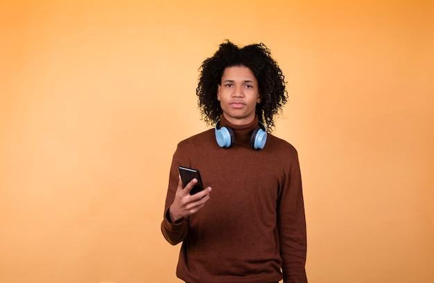 Jeune Homme Afro-américain Avec Un Casque Tenant Un Téléphone Portable Regardant La Caméra Isolée Sur Un Fond Jaune Portrait En Studio Photo Premium