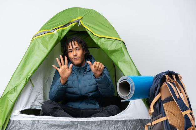 Jeune Homme Afro-américain à L'intérieur D'une Tente De Camping Verte Comptant Six Avec Les Doigts Photo Premium