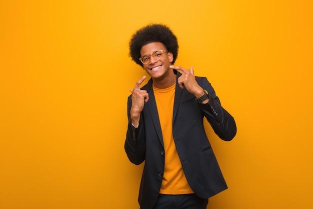 Jeune Homme Afro-américain Sur Un Mur Orange Sourit, Pointant La Bouche Photo Premium