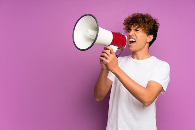 Jeune homme afro-américain sur mur violet isolé criant à travers un mégaphone Photo Premium