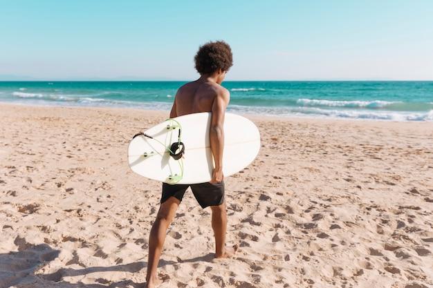 Jeune homme afro-américain avec planche de surf sur la plage Photo gratuit