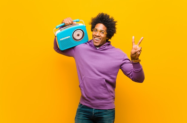 Jeune homme afro-américain avec une radio vintage contre orange b Photo Premium