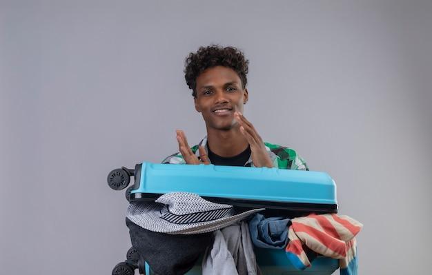 Jeune Homme Afro-américain Voyageur Debout Avec Une Valise Pleine De Vêtements Regardant La Caméra Applaudissant Souriant Sympathique Sur Fond Blanc Photo gratuit