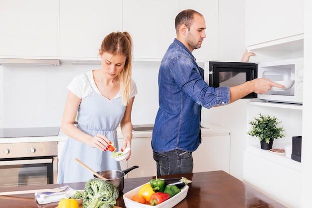 Jeune homme aidant sa femme à préparer la nourriture dans la cuisine Photo gratuit