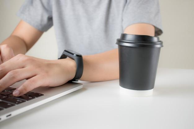 Jeune homme à l'aide d'un ordinateur portable avec du café au bureau. vue de côté Photo Premium