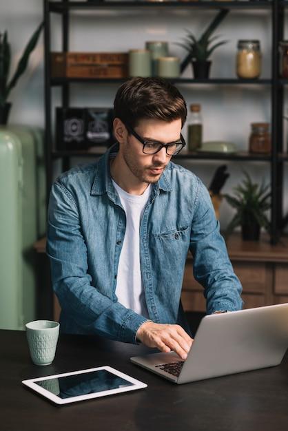 Jeune homme à l'aide d'un ordinateur portable avec une tasse de café et une tablette numérique sur le comptoir de la cuisine Photo gratuit