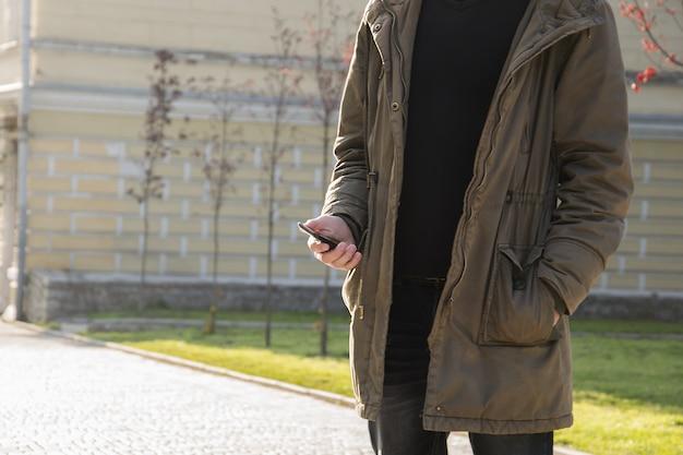Jeune homme à l'aide de son téléphone portable dans la rue Photo Premium