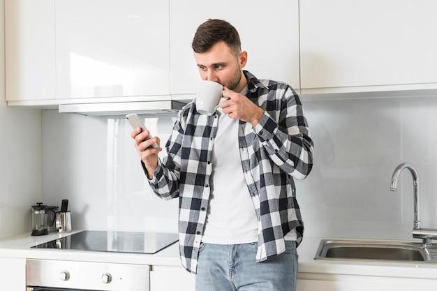 Jeune homme à l'aide d'un téléphone portable tout en buvant du café dans la cuisine Photo gratuit