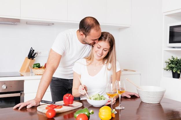 Jeune homme aimant sa femme préparant la salade dans la cuisine Photo gratuit